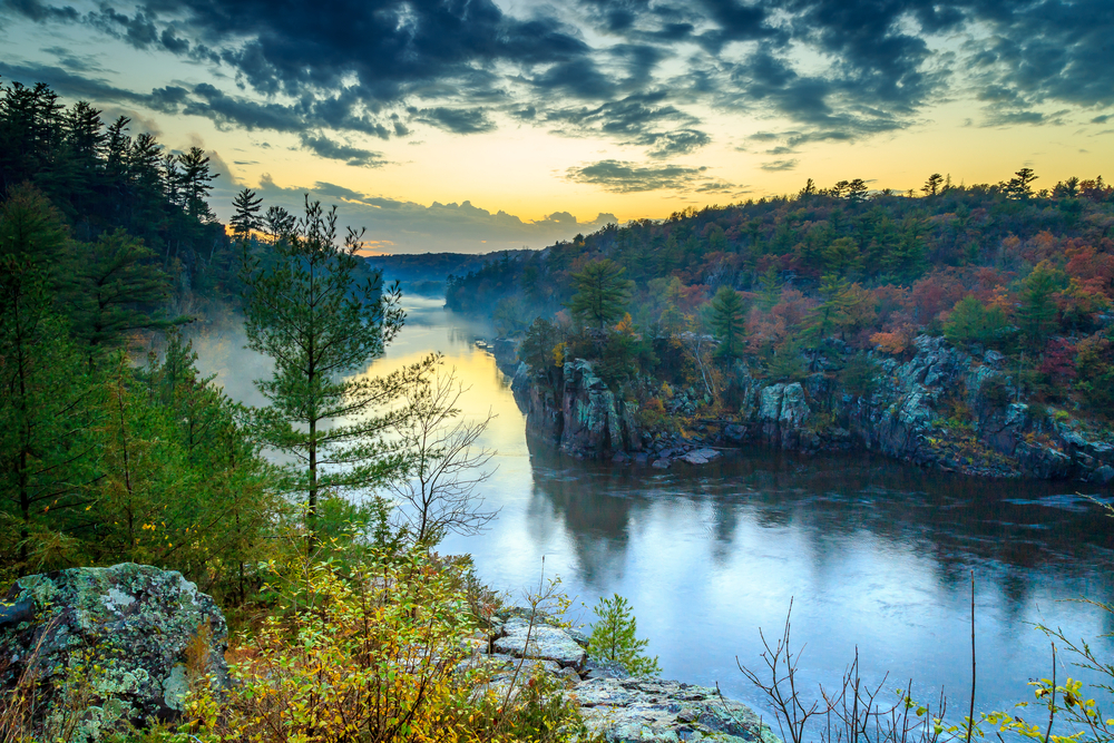 A misty river surrounded be small cliffs and fall foliage