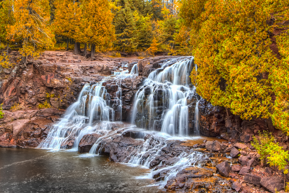 A large rocky waterfall with many splits in it. The cliff is very rocky and surrounded by trees. The trees all have yellow and orange leaves, with some of the leaves are still green. It is a beautiful fall in Minnesota view.