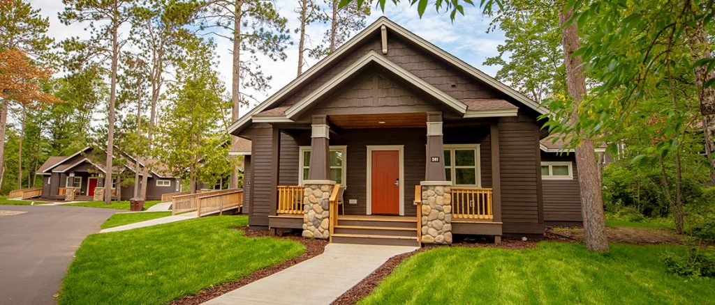 The exterior of a cottage you can rent at the Grand View Lodge resort in Minnesota. It is brown with a small front porch, a red door, and lots of windows. It has a nice yard in front of it and is surrounded by trees.