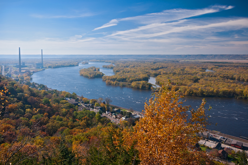 An aerial view of the Mississippi River with a town on the edge of the river. You can see lots of trees that are changing in the fall and have red, orange, yellow, and green leaves.