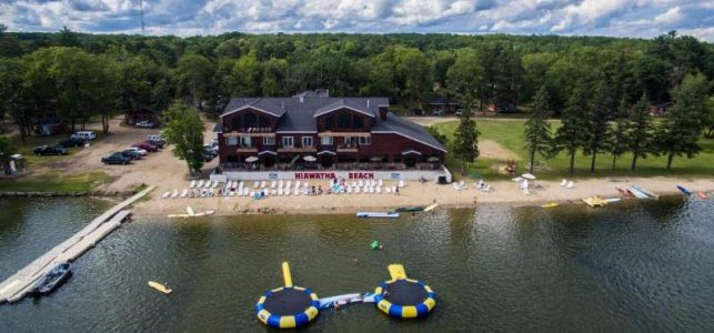 An aerial view of the main lodge of the Hiawatha Beach Resort. You can see the beach on  the lake with chairs, water trampolines, and kayaks. The area is surrounded by trees