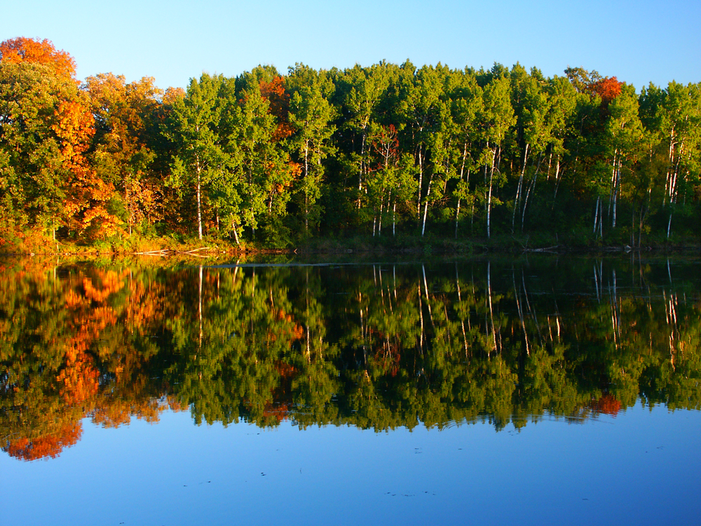 A lake with trees on the shore at Kettle Moraine State Park. The trees are mostly green, but a few have red, orange, and yellow leaves. The trees are reflected in the water of the lake.