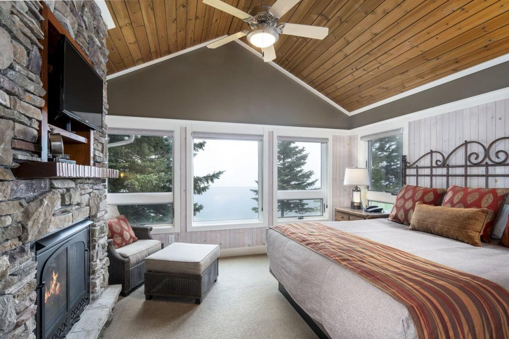 The interior of a cottage on Lake Superior. It is very cozy with shiplap walls, a large stone fireplace across from a king-sized bed, a wooden ceiling, and large windows with a view of the lake.