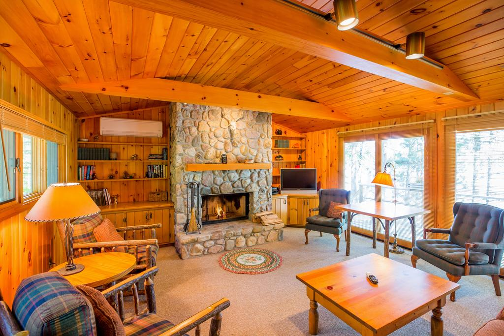 The interior living room of a cottage at a lake resort. It has plenty of seating, a large stone fireplace, wood plank walls and wood beams on the ceiling. There are also lots of windows.