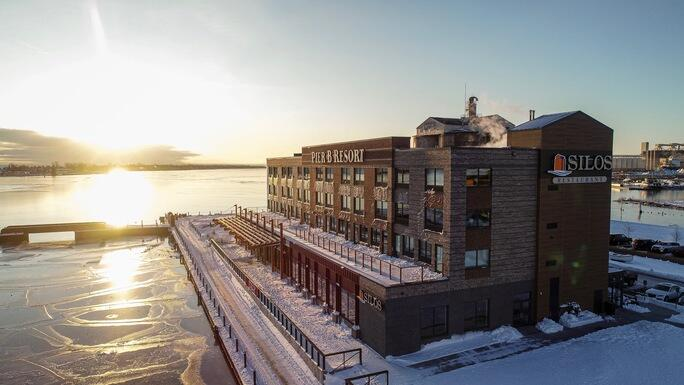 The exterior of a resort on a pier in Lake Superior that looks like it used to be a shipping building. It has rows of windows, a patio, and more. It is covered with snow and the lake looks frozen at sunset.