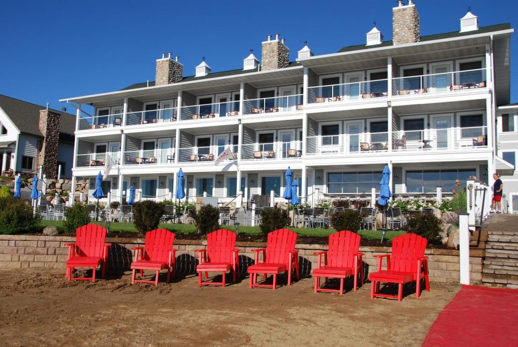 The exterior of a white resort building. There are private terraces with patio seating and a patio on the grounds as well. On the beach there are bright red Adirondack chairs you can relax in.