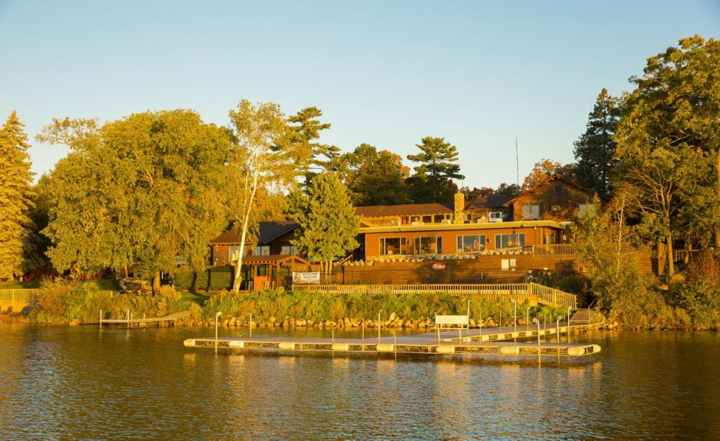 The view of a lake resort from across the lake. The resort has a large dock on the lake, a patio, and lots of windows. It is surrounded by trees and greenery and it is the golden hour.