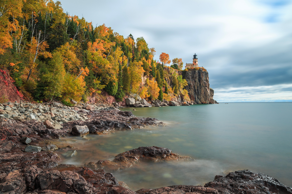 The view from the shore of a lake of the Split Rock Lighthouse. The lighthouse is perched on a rocky cliff and looks to be a peachy color and black. Behind it is a dense forest full of trees that come to the rocky shore line. The trees have yellow, orange, and green leaves. The sky is cloudy.