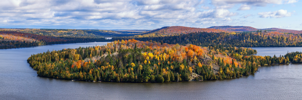 The view of the landscape at Superior National Forest. There is a large body of water surrounded large mountains and hills. The landscape is full of dense forest and goes on for miles. The trees in the forest are green, yellow, red, and orange. The sky is light blue with big fluffy clouds
