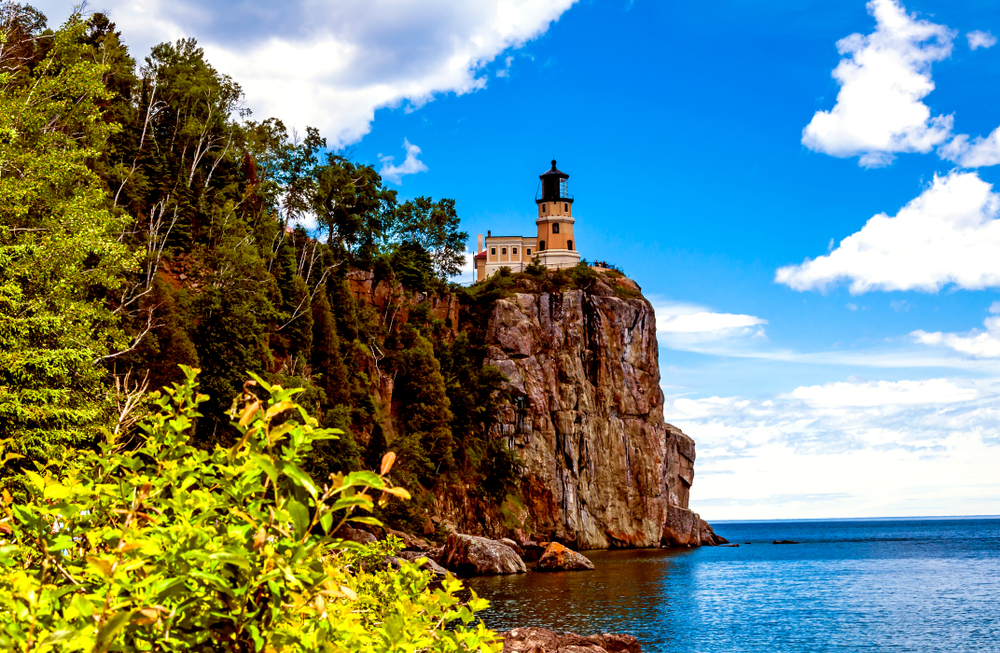 A lighthouse on the top of a cliff overlooking the lake