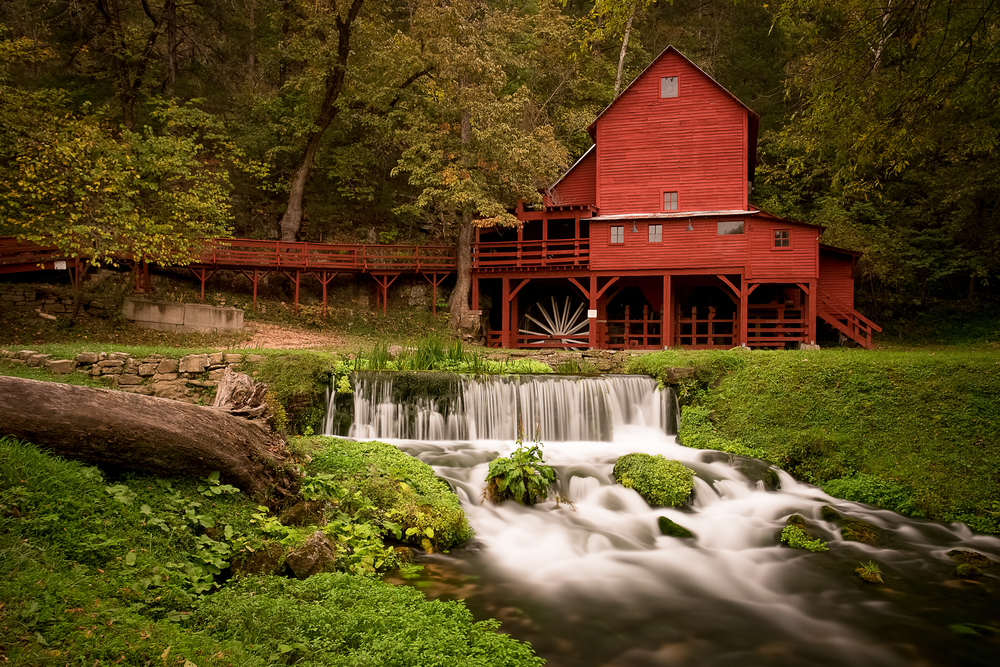 Rural red grist mill with wide waterfall surrounded by green trees.
