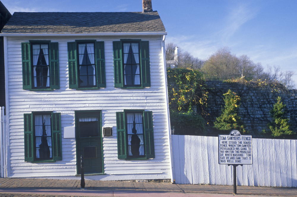 White wood-plank house with green shutters, white fence with historical marker in front of it. Things to do in Missouri.