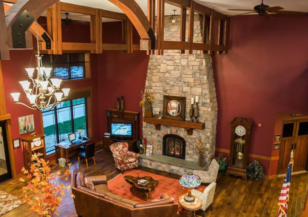 The interior of a common room at the Timberlake Lodge. It has a large stone fireplace, a wooden beam ceilings, and a large leather couch near the fire. It is a great resort in Minnesota.