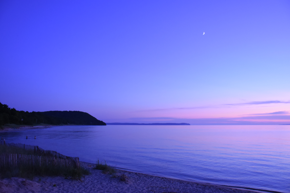 Beautiful purple sky and  calm waters on Michigan beach, with sand and grassy hills in foreground.