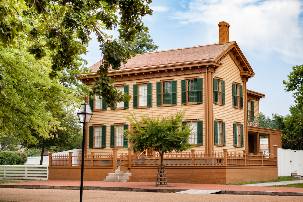 The exterior of the Abraham Lincoln House National Historic Site. It is a two story home with a creamy orange exterior, green shutters on all the windows, and a clay colored roof. There is a brick and wooden fence around it that is a clay color. There are trees in front of the house.