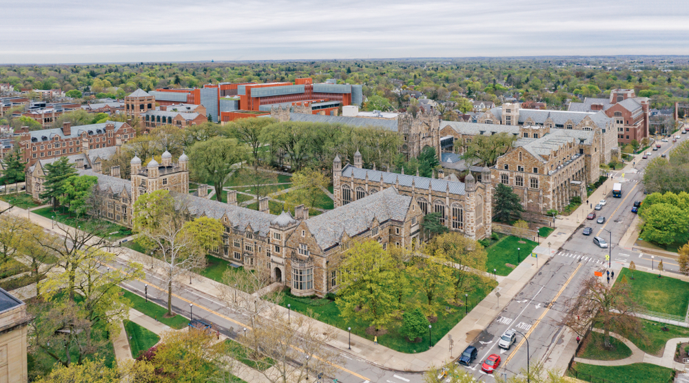 An aerial view of one of the campus buildings in Ann Arbor. It is a gothic style building in the shape of a square. There is a large courtyard in the middle of the buildings. You can see more buildings and trees near the larger complex.