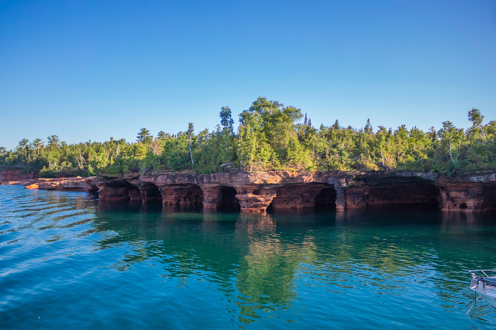 A view of the shore of one of the Apostle Islands. The shore is made up of rocky caves and cliffs with green trees growing on them. The water and the sky are both very blue.
