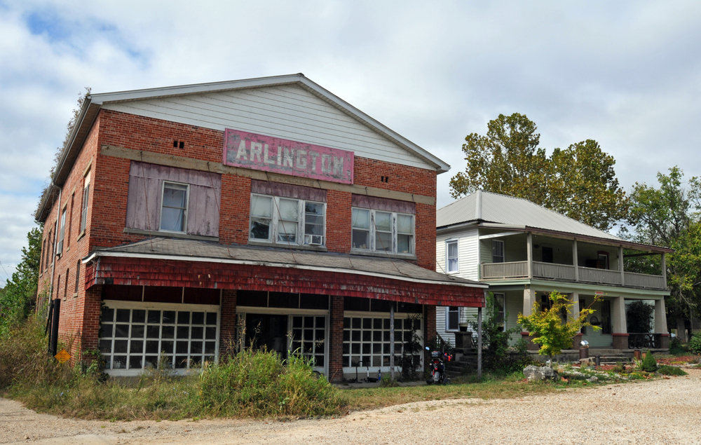 An abandoned brick building in the ghost town of Arlington. The building has a faded red sign that says 'Arlington', windows with white trim missing the glass, and boarded up windows. Beside it is a white dilapidated house.