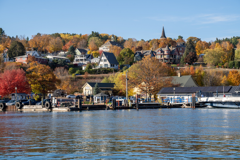 The view of the small town of Bayfield from the lake. It has lots of charming buildings going up the side of the hill and trees with brown, yellow, orange, red, and green leaves. There is also a dock area on the water.