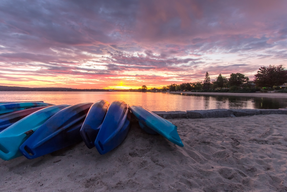 Kayaks on the sand with the water and tress in the background. Clinch Park has one of the best beaches in Traverse City