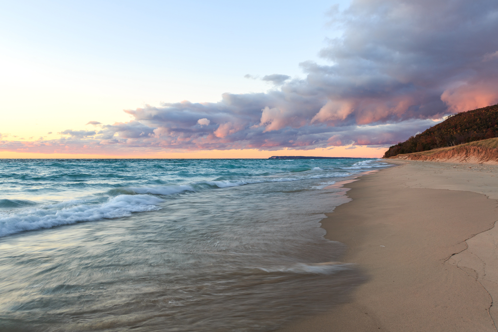 A beautiful beach with a sand dune in the distance at sunset. One of the best beaches in Traverse City
