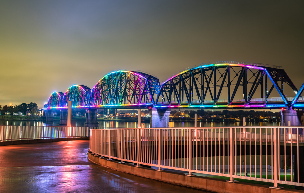 The Big Four Pedestrian Bridge all lit up in rainbow colors at night. You can see the bridge from a paved walkway next to the river. Across the river you can see a city lit up at night.