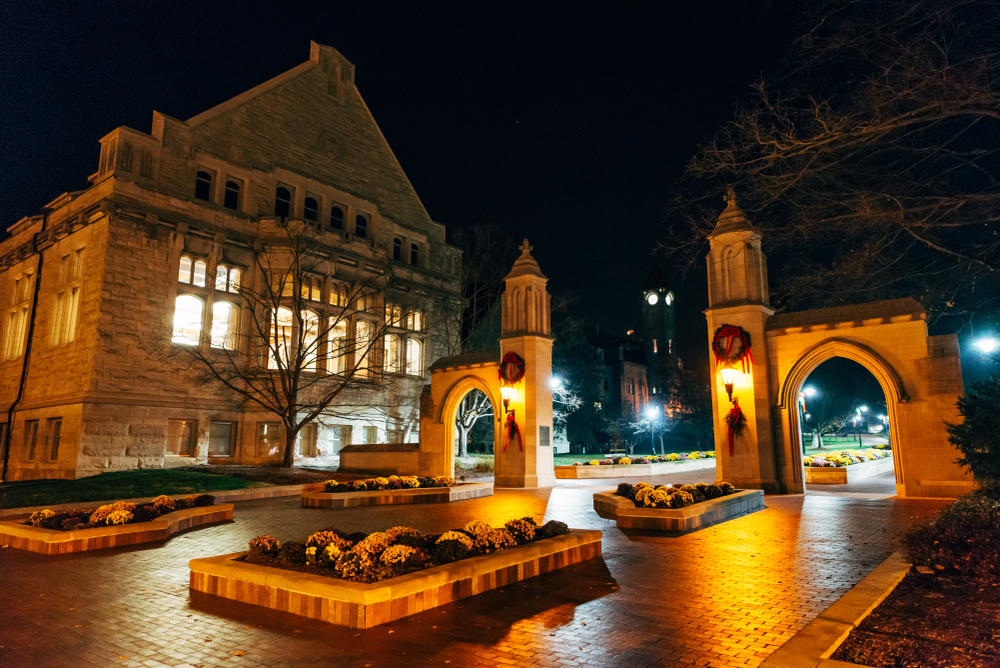 A courtyard in Bloomington Indiana. It is decorated for Christmas with wreaths and boughs of holly on the archway entrance. It is dark and the sconces on the archway are lit up and the old building next to the courtyard is also lit up.
