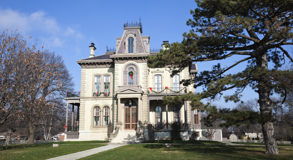 The exterior of the David Davis Mansion in Bloomington Illinois. It is a Victorian style mansion that is cream with pale grey accents. It has wreaths in the windows and garland on the porches like it is decorated for Christmas. Around the mansion there is a green lawn and some trees.