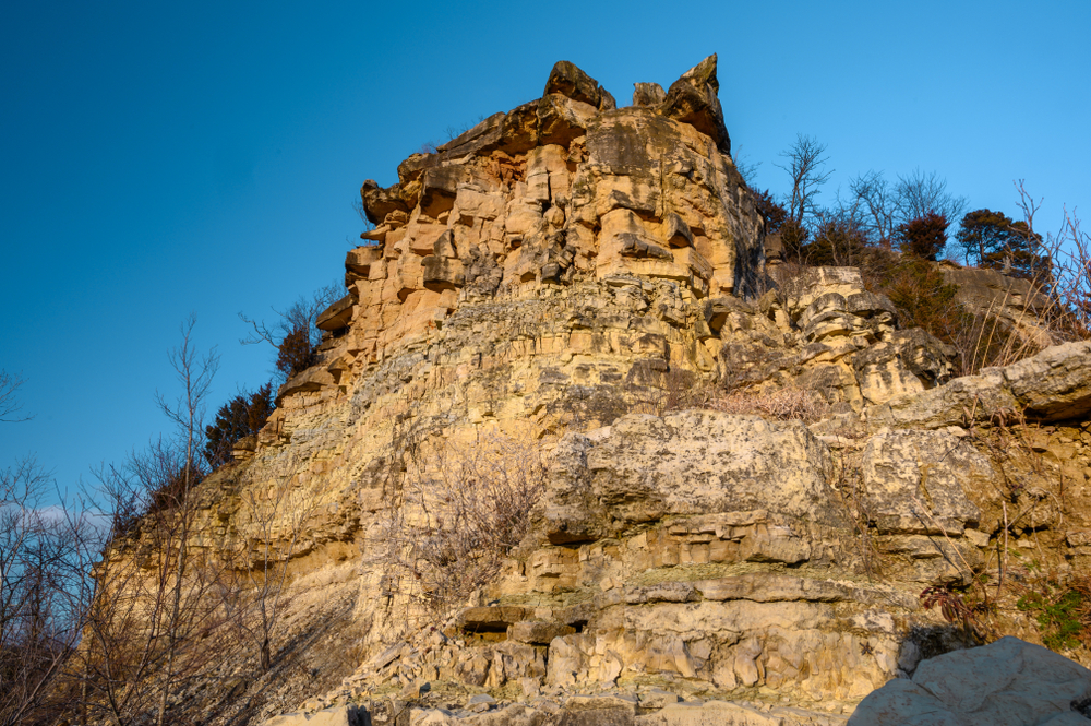 The larges stone bluff at Klondike Park. It is a sandy color stone and has trees with no leaves or brown leaves all over it. The sky is very blue.