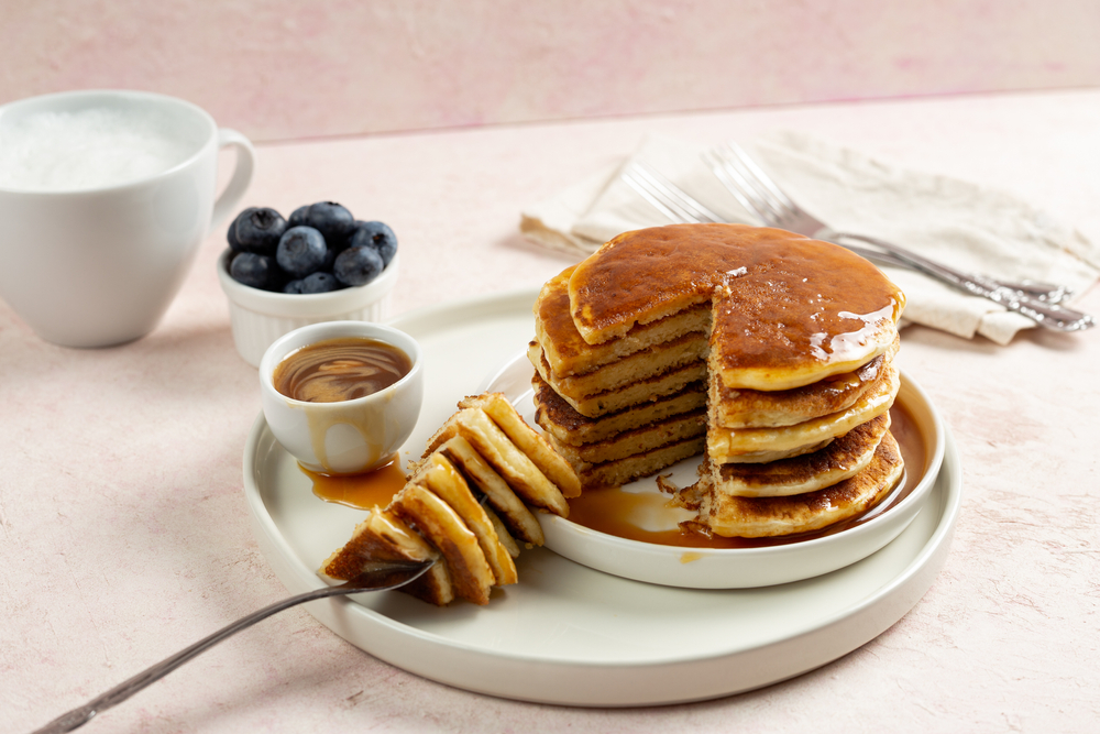 Pancakes piled high on a plate with blueberries and maple syrup