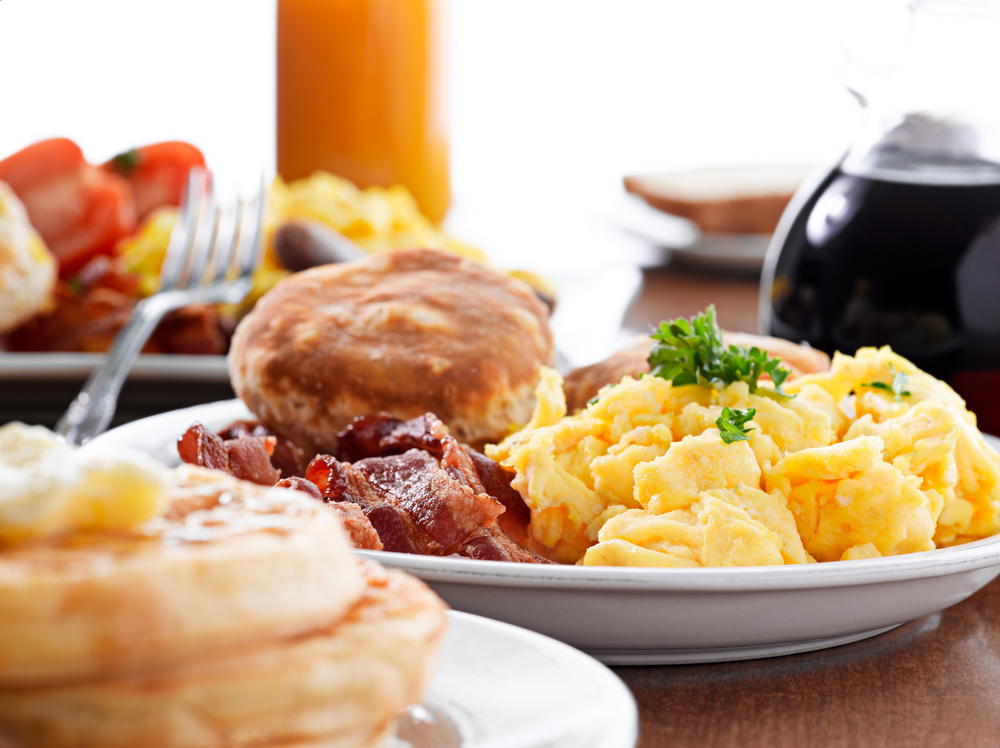 A huge american breakfast with eggs and biscuits on a table with coffee and crumpets