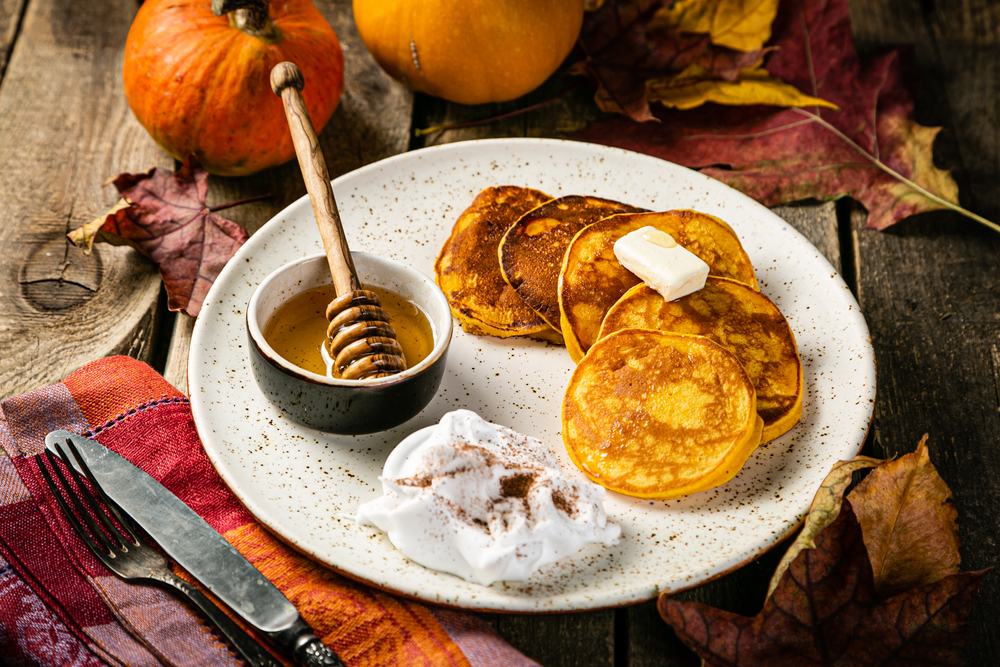 Pumpin pancakes on a plate with syrup and pumpkins