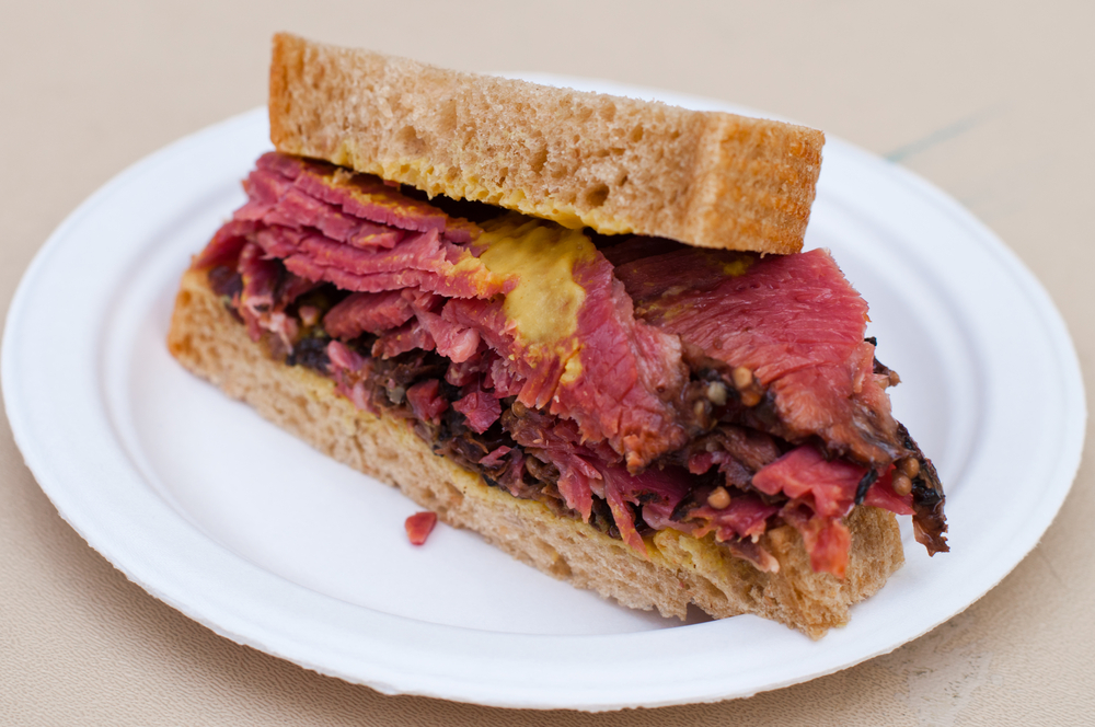 A Corn Beef with Beetroot Sandwich on a white plate