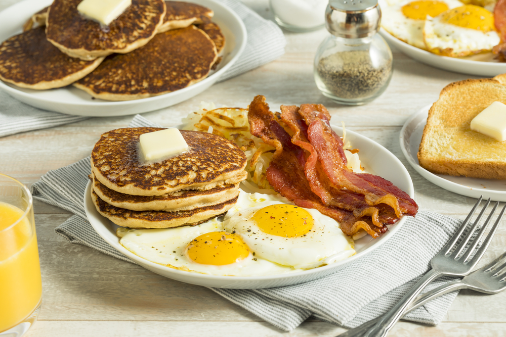 Pancakes, eggs and bacon on a breakfast table