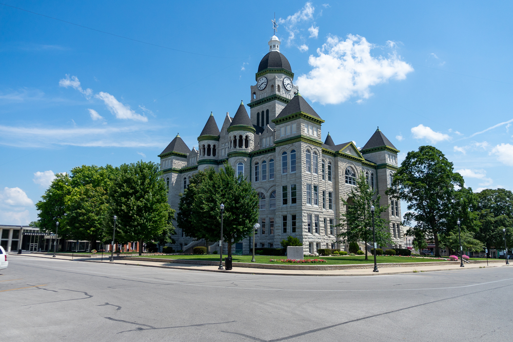 The court house in the small town of Carthage. It is a large stone building with gray stone, green trim, and a clock tower. Around it is a green lawn and trees. One of the best Missouri road trips stops