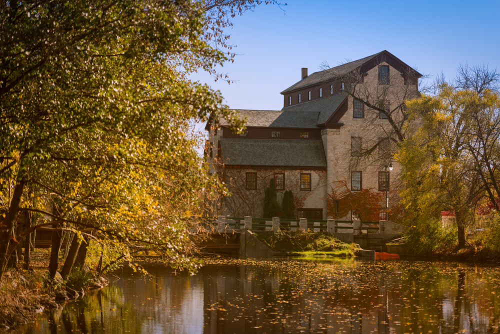 An old Grist Mill on the river in Cedarburg. It is a large building made of stone. It is on the river and the river has leaves in it. Around the river are trees with yellow and brown leaves.