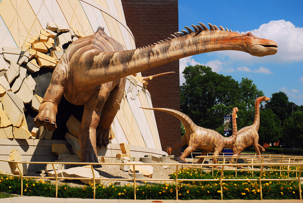 A large dinosaur that looks like its breaking out of the side of a building. There are also two other smaller dinosaurs in the background. It is a sunny day with clouds in the sky. One of the best things to do in the Indiana.