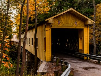 A yellow colored bridge on a road in the autumn foliage. Windsor Mills in one of the covered bridges in Ohio