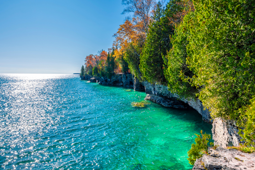 A view looking down the shore of one of the islands at Cave Point State Park. The shore is large rock formations covered in trees with green, yellow, orange, and some red leaves. The water is very blue.