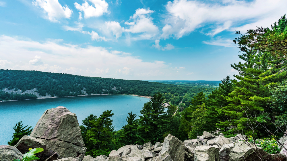 The view looking over a rocky cliff down into a very blue lake in Wisconsin. The lake is surrounded by tall trees with green leaves. The sky is very blue and there are there some clouds.