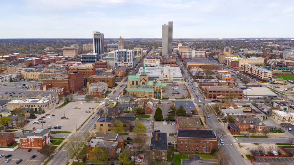 An aerial view of the city of Fort Wayne. You can see buildings, homes, and churches. A little bit in the distance you can see smaller skyscrapers. It is overcast and cloudy.