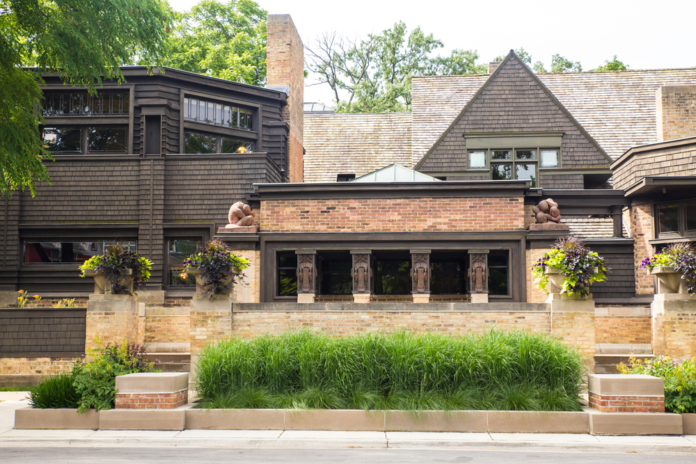 The front exterior of the Frank Lloyd Wright house and studio. It is a multi layered brick building with dark wood shingles on the sides of a few of the peaks. There is a small garden in front of it with tall green grass and plants in planters with green and dark purple vines and purple flowers.