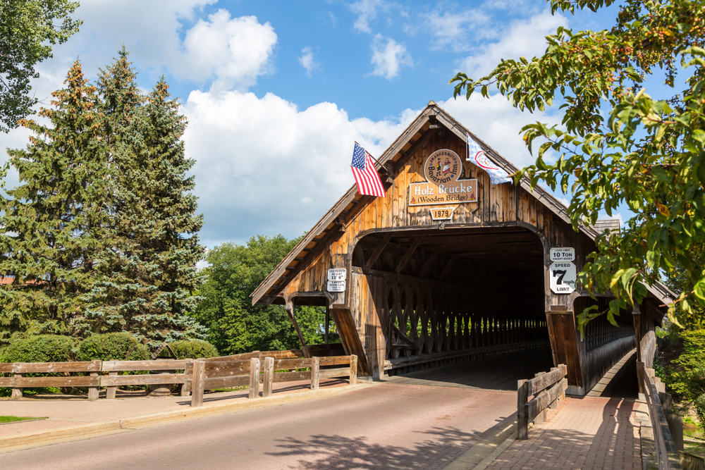 A covered bridge outside of the town of Frankenmuth. It is a classic wooden style bridge with a classic Dutch sign on it. There are trees surrounding the bridge and the sky is sunny with fluffy white clouds.