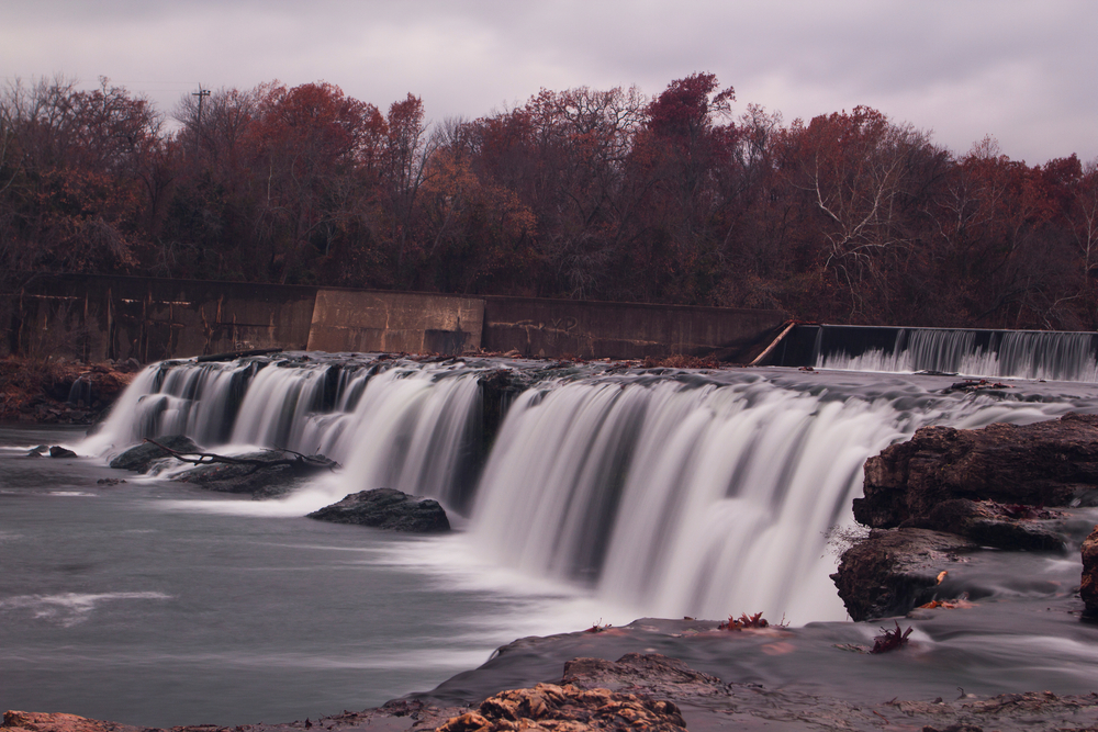 The Grand Falls in Joplin which is a large multi cascading waterfall. The sky is dark and the trees in the background are either bare or they have brown leaves.