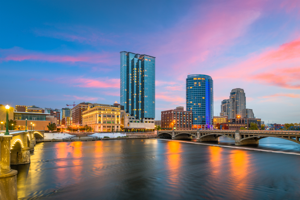 A view of the skyline of Grand Rapids at twilight. All the buildings are lit up, you can see snow on the ground, and the lake looks frozen. The sky is blue, pink, and purple. It is one of the best things to do in Michigan.