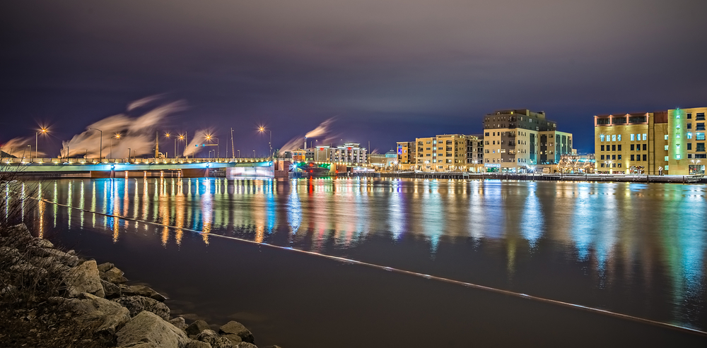 The view of the Green Bay skyline from the river at night. All the buildings are lit up and there is smoke billowing from nearby smokestacks. The skyline is reflected in the river.