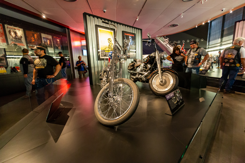 People wearing typical 'biker gear' looking at the motorcycles in the Harley Davidson Museum. There are motorcycles, framed vintage advertisements, and more in the room.