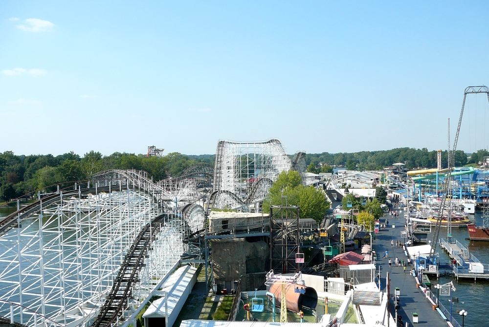 A slight aerial view of the Indiana beach amusement park. You can see a large white roller coaster, boats in the lake, a paved walkway, and various other rides. It is a sunny day.