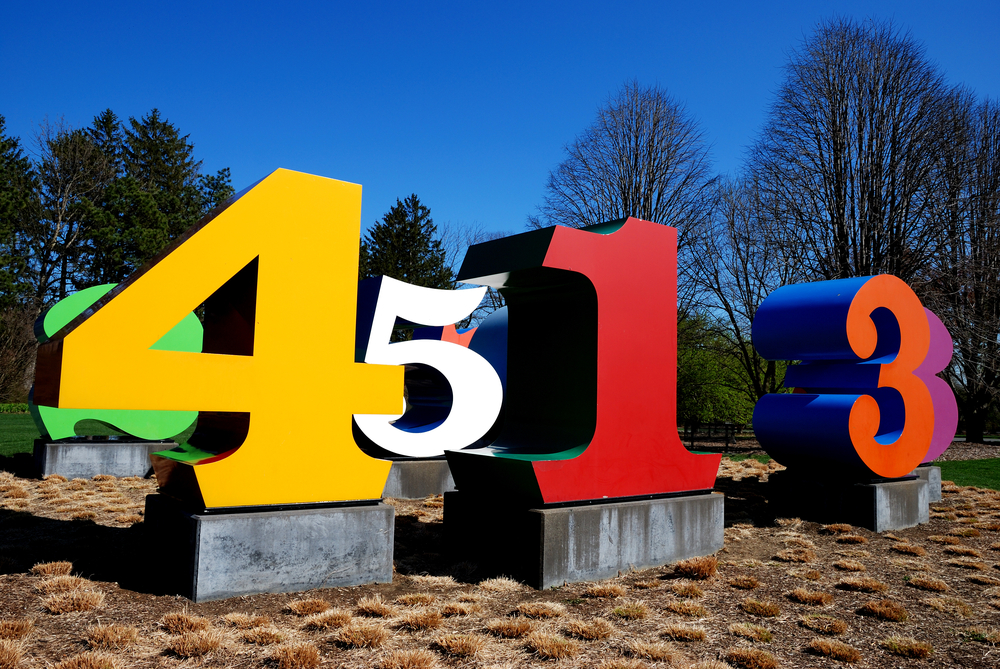 Colorful sculptures of numbers in the garden outside of the Indianapolis Museum of Art. The sculptures are on a patch of dirt with dead plants around it. Behind the numbers you can see trees but most of them have no leaves.