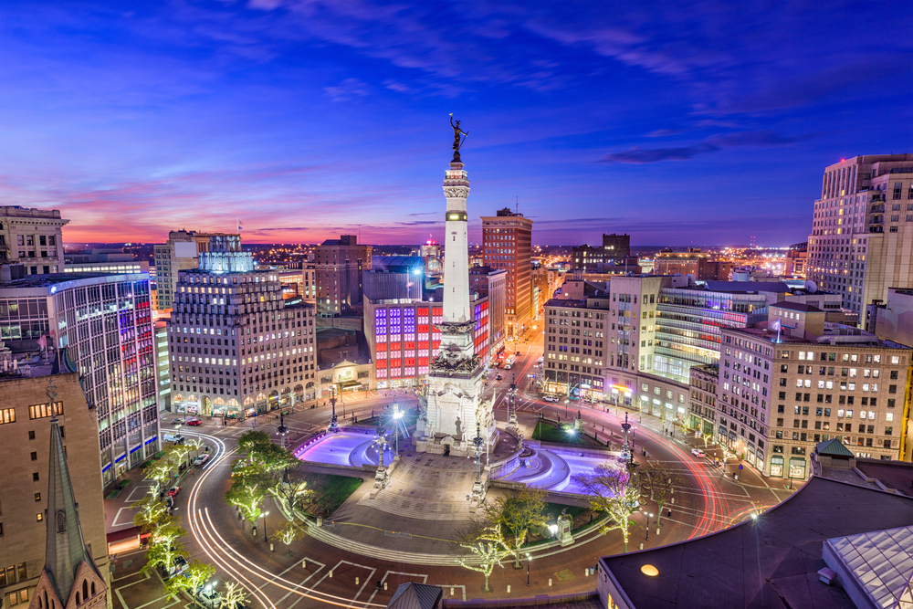The city center of Indianapolis at twilight. The buildings are all lit up and you can see the light trails of cars on the road. The sky is a dark blue, pink, and purple. It is one of the best things to do in Indiana.